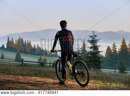 Back View Of Male Cyclist In Cycling Suit Standing With Bike In The Morning. Man Bicyclist Enjoying