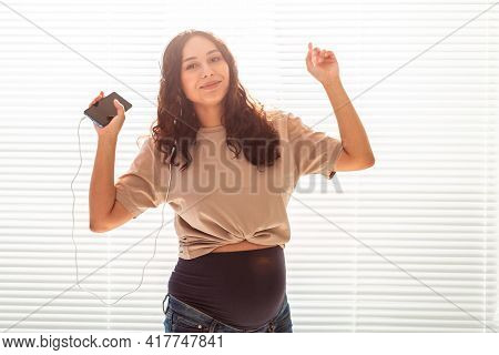 Curly-haired Brunette Pacified Pregnant Woman Listens To Music Using Smartphone And Headphones. Conc