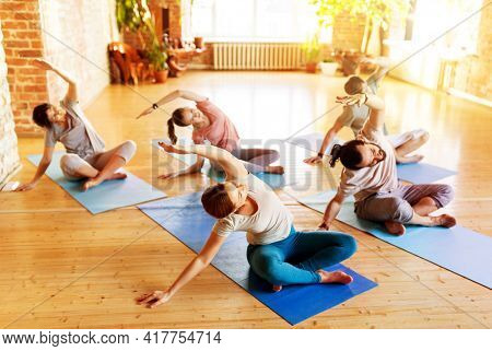 fitness, sport and healthy lifestyle concept - group of people doing yoga exercises on mats in gym or studio