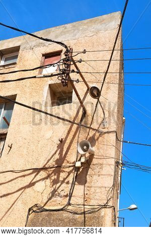 Typical electricity and electricity wires on old house in Spain
