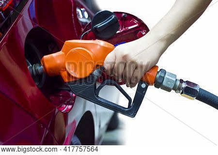 Hand Holding Pump Nozzle Is Refilling Into The Fuel Tank Of A Red Car