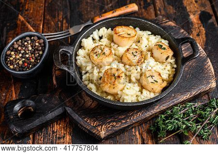 Seafood Risotto With Scallops In A Pan. Dark Wooden Background. Top View
