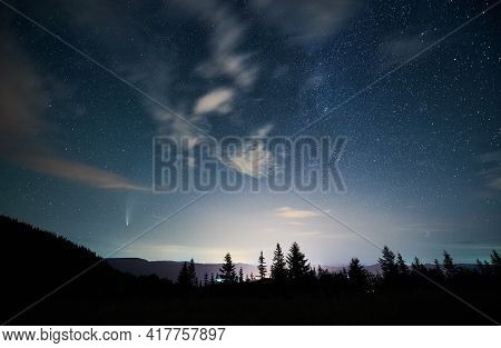 Magnificent View Of Night Starry Sky Over Coniferous Wood In Mountains. Landscape Of Mountain Forest