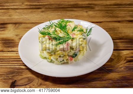 Salad With Crab Sticks, Sweet Corn, Cucumber, Eggs And Mayonnaise On Wooden Table