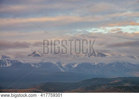 Scenic Mountain Landscape With Great Snowy Mountain Range Among Low Clouds And Forest In Valley At S