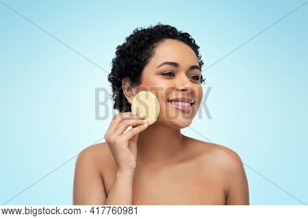 beauty, people and skincare concept - young african american woman with bare shoulders cleaning face with exfoliating sponge over blue background
