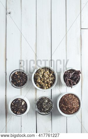 Various Herbal Infusions On White Old Wooden Board, Chamomile, Red Tea, Rooibos, Black Tea, Green Te