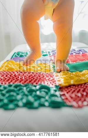 The Kid Walks Barefoot On Multi-colored Massage Rugs.
