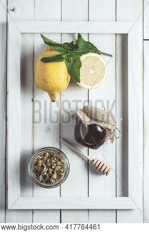 Chamomile Infusion In A Frame On White Old Wooden Board With Lemon And Jar Of Honey