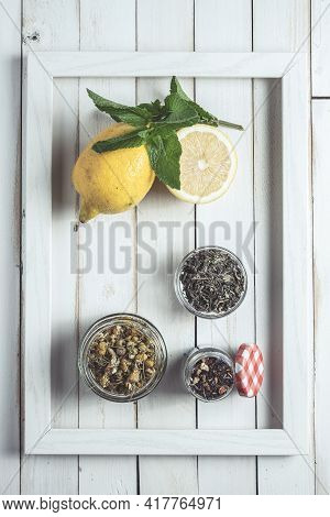 Various Infusions In A Frame On White Old Wooden Board With Lemon And Jar Of Honey
