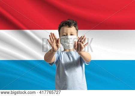 Little White Boy In A Protective Mask On The Background Of The Flag Of Luxembourg. Makes A Stop Sign