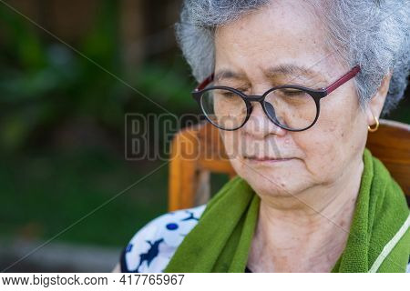Close-up Portrait Of Senior Woman Outdoors. Asian Elderly Woman Wearing Glasses And Eyes Closed Sitt