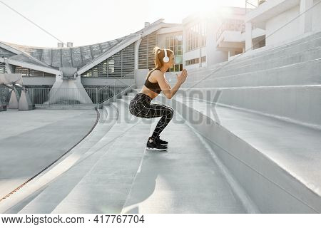 Fit Young Attractive Woman Exercising In Outdoor Arena. Interval Training By Doing Jumps And Squats