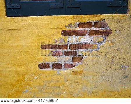 Empty Textured Yellow Plaster Wall Facade With Old Bricks Behind - Grunge Vintage Background With Sp