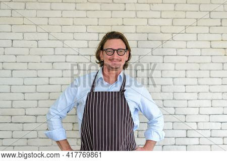 Portrait Of Happy Senior Man Gardening Wearing Glasses And Denim Apron Standing In Front Of White Br