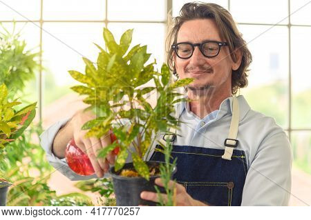 Portrait Of Happy Gardener Senior Man Wearing Glasses Taking Care Of Small Tree In Plant Pot As A Ho