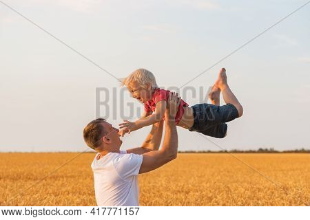 Father Playing With Son Outdoors In Field. Daddy Tosses Child Up.