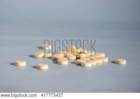 Scattering Of Round Medicinal Pills On Gray Background. Medicine Concept Of Tablets, Drugs, Medicine