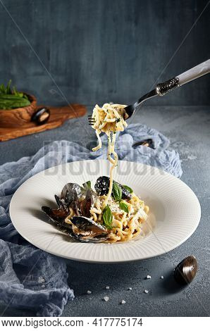 Italian Cuisine - Pasta With Mussels, Basil Leaf and Parmesan Cheese. Homemade Pasta on Fork. Blue textured table with salt and shellfish on foreground. Dark background