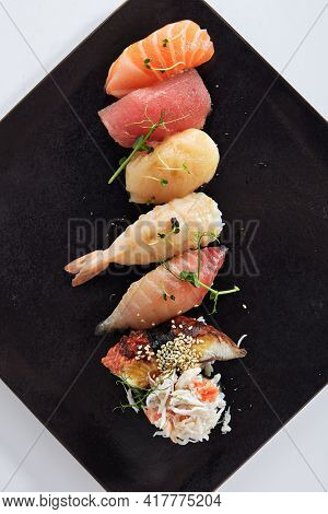 Japanese Nigiri Sushi Set - Sushi with Rice and Various Seafood. Salmon, Tuna, Sea Scallop and other seafood fish. Nigiri Sushi row on black slate platter. Isolated on white background. Top view