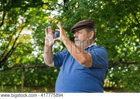 Caucasian Bearded Senior Man Using Cellular Phone Outdoor Making Photos With Internal Camera At Summ