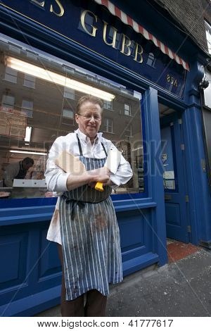 Portrait of a happy middle age man standing outside shop with cleaver