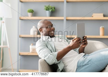 African American Man Reading E-book On Digital Tablet Or Browsing Internet, Enjoying Weekend And Res