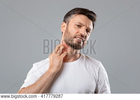 Bearded Man Scratching Neck On Grey Background, Having Annoying Itch