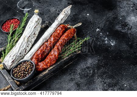 Spanish Dry Cured Sausages Salami, Fuet And Chorizo In A Wooden Tray. Black Background. Top View. Co