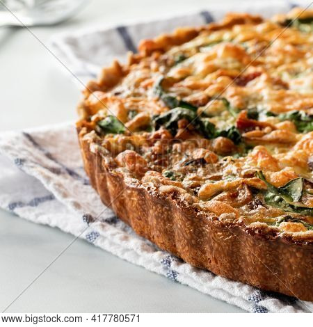 Close Up Of A Homemade Baked Spinach And Bacon Quiche On A Kitchen Towel Cooling By A Bright Window.