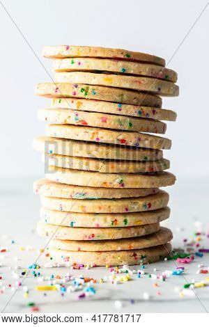 Close Up Of A Stack Of Homemade Sprinkle Sugar Cookies Against A Light Background With Sprinkles Sca