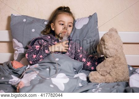 A Little Girl Is Sick And Is Treating A Severe Cough Or Allergy At Home With An Inhaler. An Inhaler