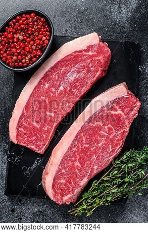Raw Cap Rump Steak Or Top Sirloin Beef Meat Steak On Marble Board. Black Background. Top View