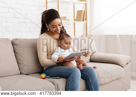 Cheerful Black Mommy Using Digital Tablet Holding Baby At Home