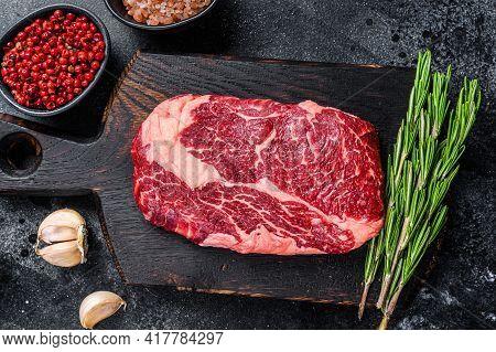 Black Angus Ribeye, Raw Rib-eye Beef Steak On A Wooden Board With Knife. Black Background. Top View
