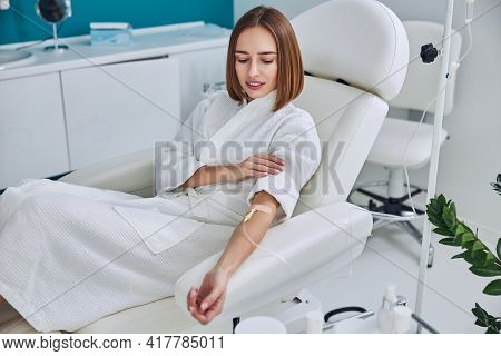 Happy Cheerful Young Lady Resting At The Intravenous Vitamin Drip Treatment In Spa Salon