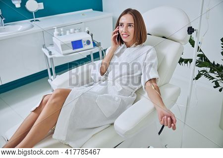 Charming Pretty Caucasian Female Sitting In Armchair While Receiving Intravenous Vitamin Drip Treatm
