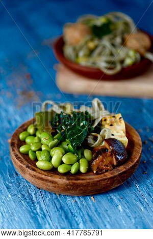 a wooden dish with some edamame beans, spelt tagliatelle, tofu, kale and shiitake mushrooms, on a rustic blue wooden table next to another plate with spelt tagliatelle, kale and vegan meatballs