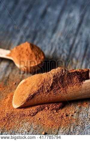closeup of a wooden measuring scoop and a wooden spoon full of camu-camu powder on a gray rustic wooden table