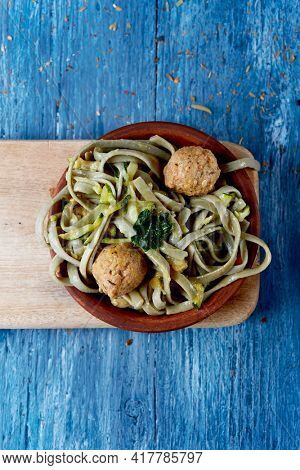 high angle view of an earthenware plate with some spelt tagliatelle with kale and vegan meatballs, on a rustic blue wooden table