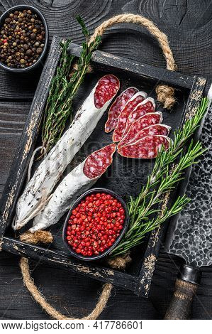 Fuet Salami Sausage Slices With Thyme And Rosemary In A Wooden Tray. Black Wooden Background. Top Vi