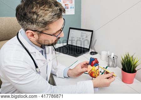 Treatment Of Heart Disease. Mature Cardiologist Using Medical Anatomical Model Of A Human Heart For
