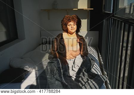 Beautiful Curvy Plus Size African Black Woman Afro Hair On Bed With Grey Plaid Blanket Cozy Bedroom
