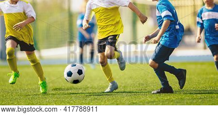Group Of School Boys Playing Football Tournament Match On Stadium. Kids Soccer League