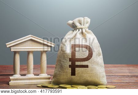 Russian Ruble Money Bag And Bank / Government Building. Tax Collection And Budgeting. Monetary Polic