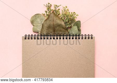 Sketchbook Notepad Mocap On Pink Background With Eucalyptus Branch And Ficus Leaf. Empty Sheet, Plac