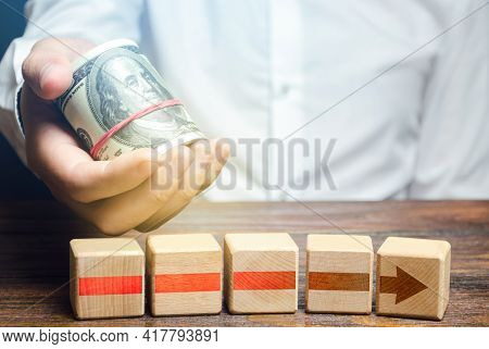 Man Holds Money Above Of Blocks Of Red Arrow. Financing And Investing In Completion Of A Business Pr