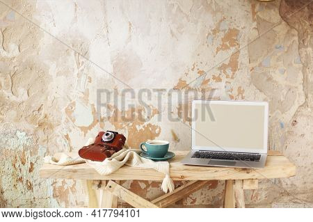 Retro Photo Camera And Cup Of Fresh Coffee Placed On Knitwear Near Modern Netbook With Blank Screen