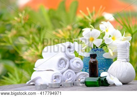 Spa Treatments On Wooden Table And Spa Candle Light Atmosphere In Wellness Centre. Beauty Spa Treatm