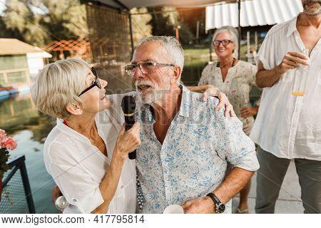 Senior People Celebrating Birthday In The Cottage On The River Singing Karaoke.